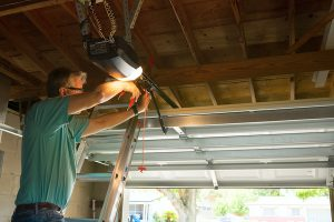 Professional automatic garage door opener repair service technician man working on a ladder at a home residential location making adjustments and fixing it while installing it.